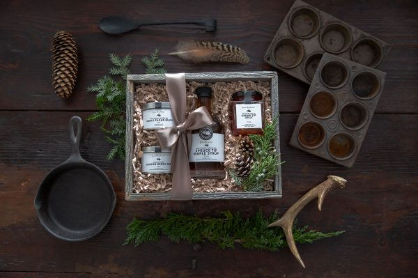 Flatlay of natural food products in rustic box surrounded by vintage cooking tools and natural branches and antlers