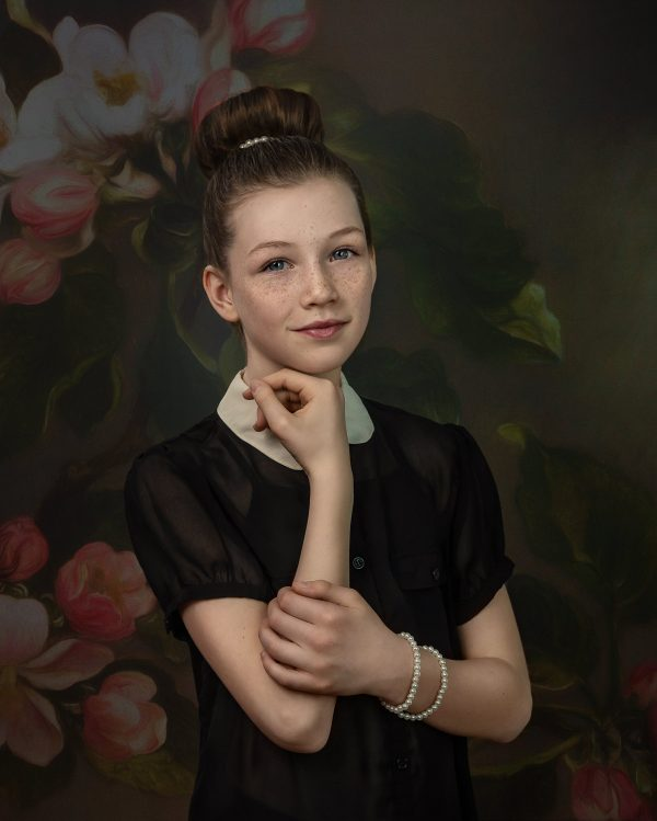 portrait of girl wearing pearls with bun in her hair using a digital background of apple blossoms