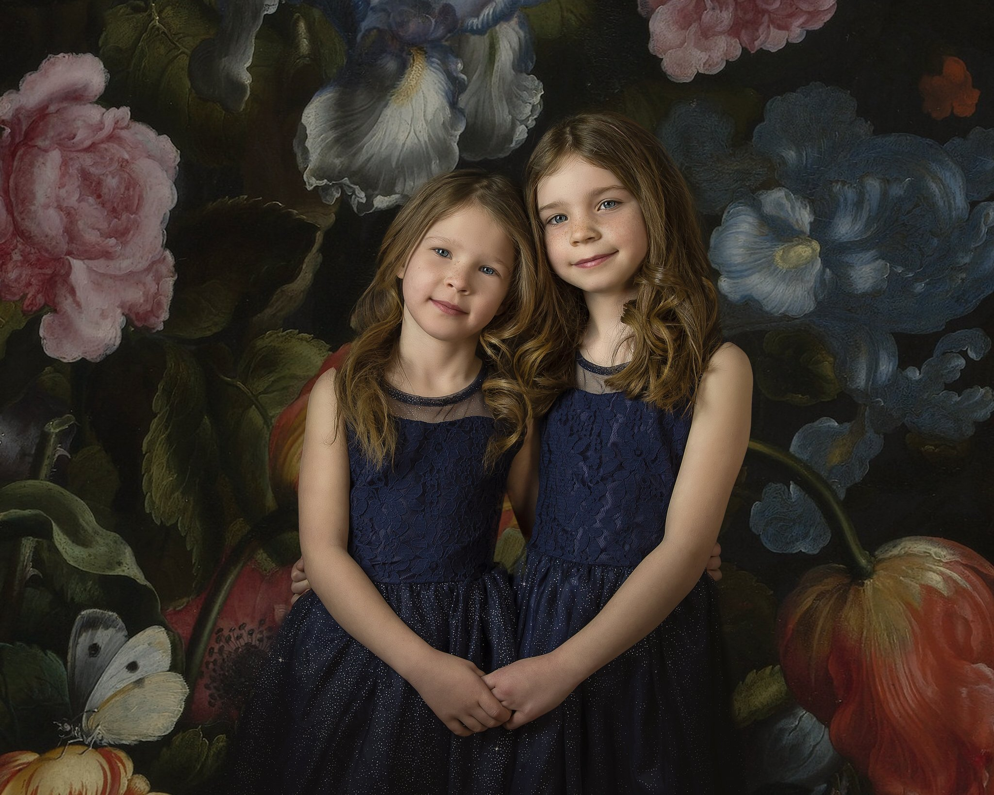 family portrait of two sisters wearing navy blue dresses with a digital floral background