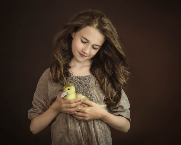 portrait of girl holding a yellow duckling