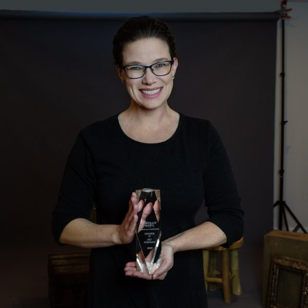 Portrait photographer Alana Lee holding her first place award in the Portrait Masters Pets category