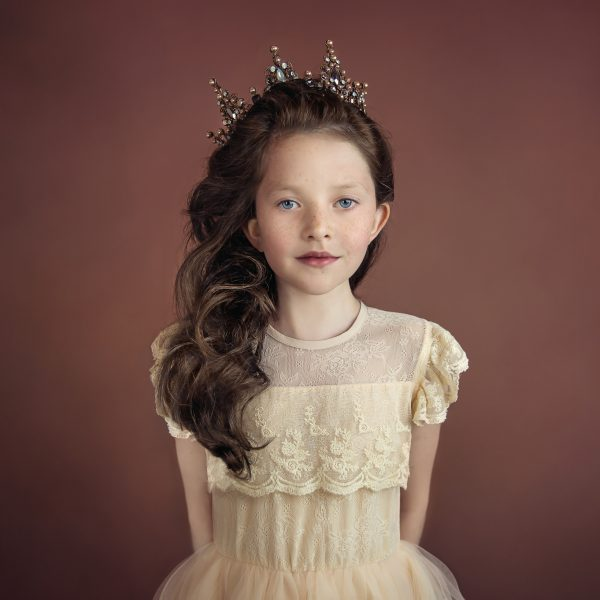 portrait of girl with curly brown hair wearing vintage lace dress and princess crown