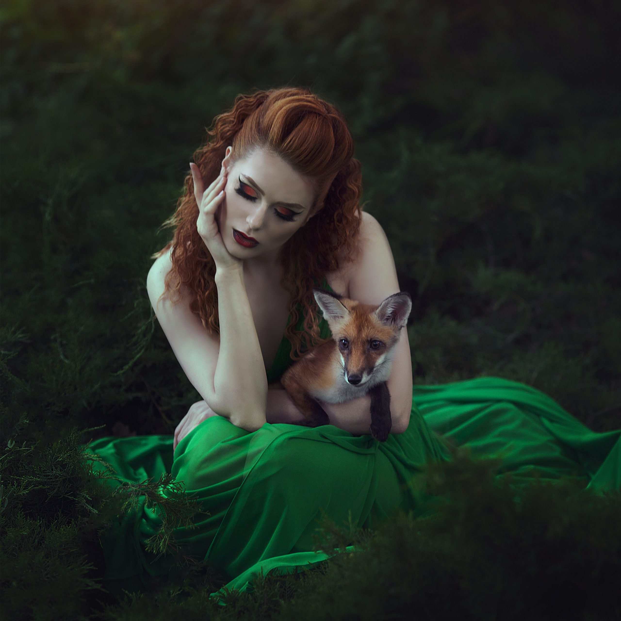 fantasy image of red haired woman with dragonfly wings in forest holding a fox