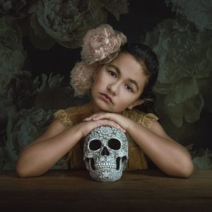 portrait of young girl resting on skull with flowers in her hair and painterly floral background