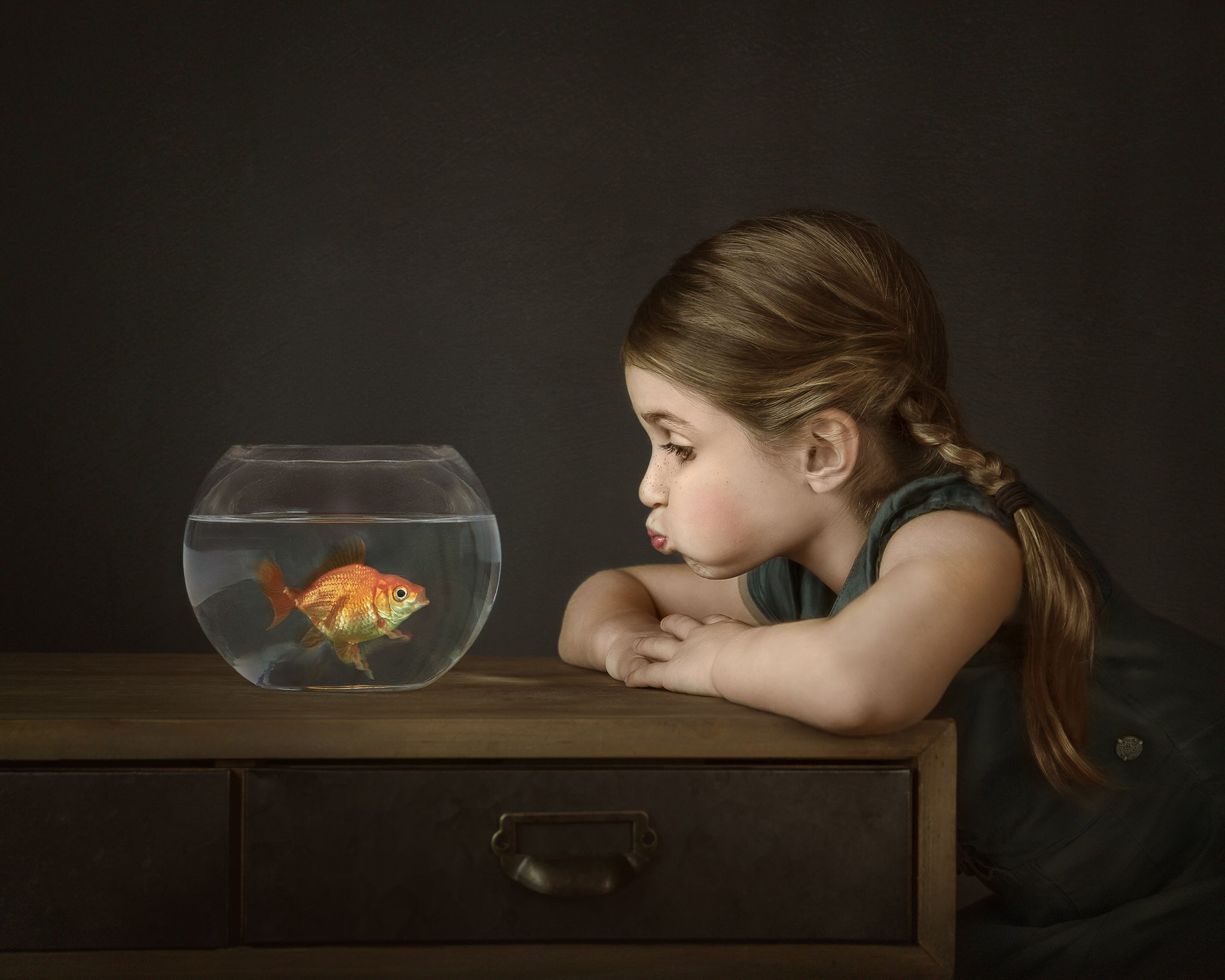 girl making fish lips looking at a goldfish in a bowl