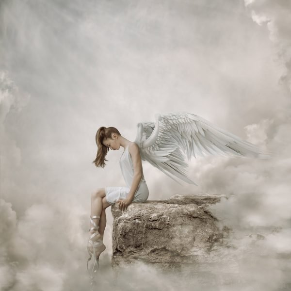 girl in white dress with ballet ribbons and angel wings sitting on the edge of a cliff in the clouds