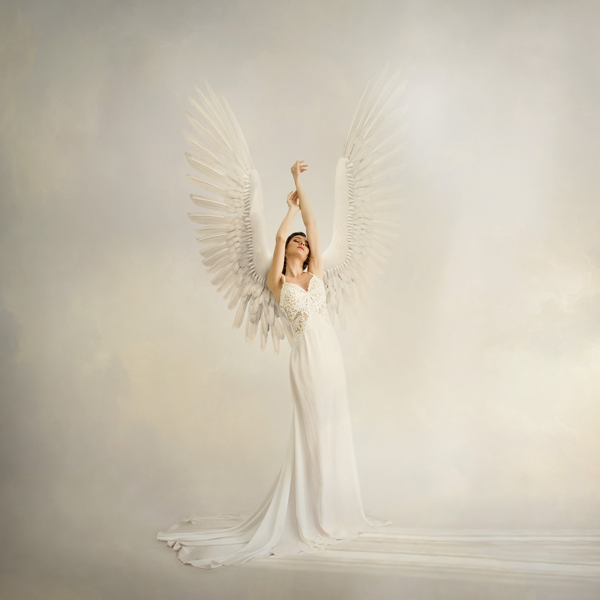 woman in white dress with angel wings in clouds