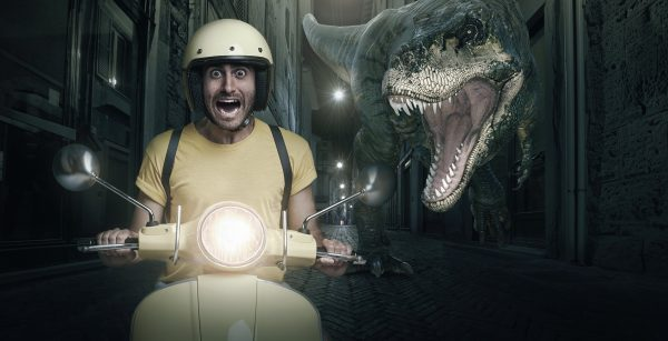 A photoshop composite image of a man on a yellow scooter being chased by a tyrannosaurus rex through city streets with colors featuring Pantone 2021 color of the year yellow and grey