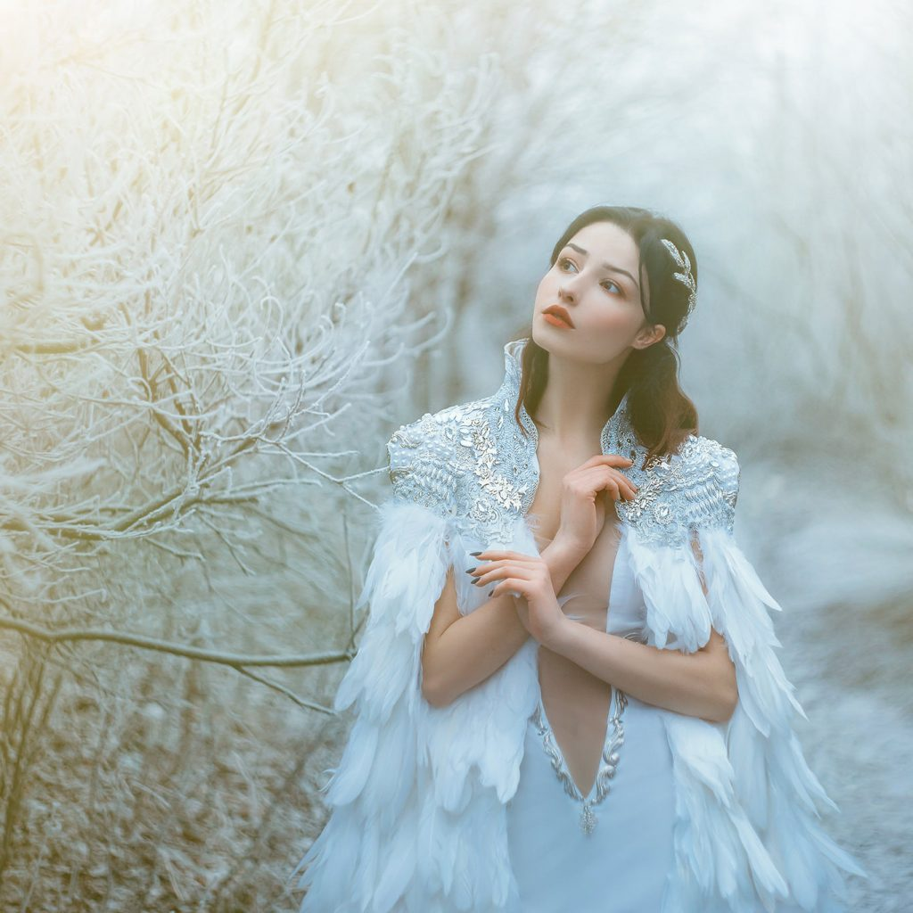 fantasy style photo of woman in feather gown with beautiful winter light overlay