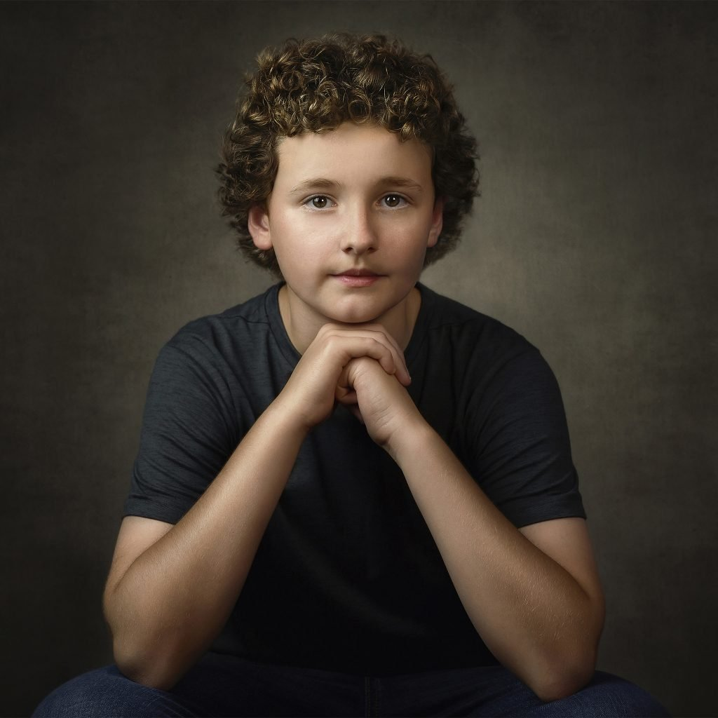 young boy posing in studio in front of a traditional style digital background