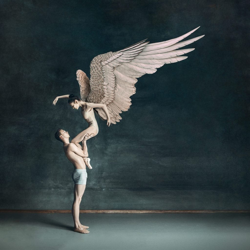 Two dancers in dramatic pose with digital wing overlay