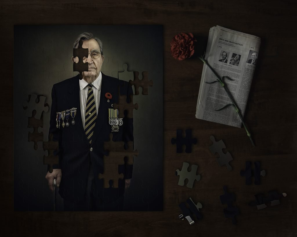 korean war veteran portrait made into a puzzle on a table with carnation and obituary announcement