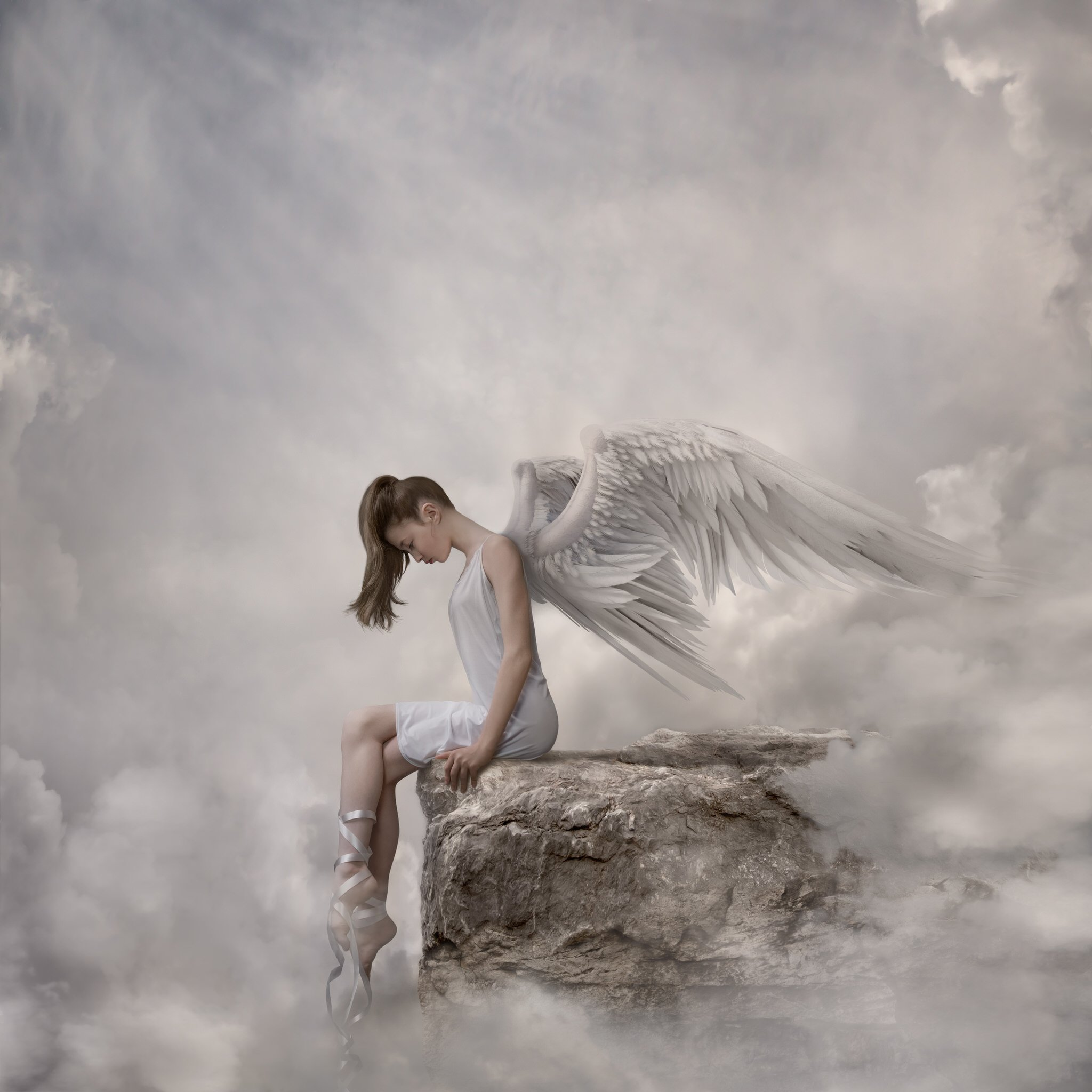 girl in white dress and angel wings sitting on the edge of a cliff in the clouds