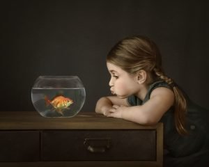 award winning image of young girl looking at a goldfish in bowl with a fish lips expression