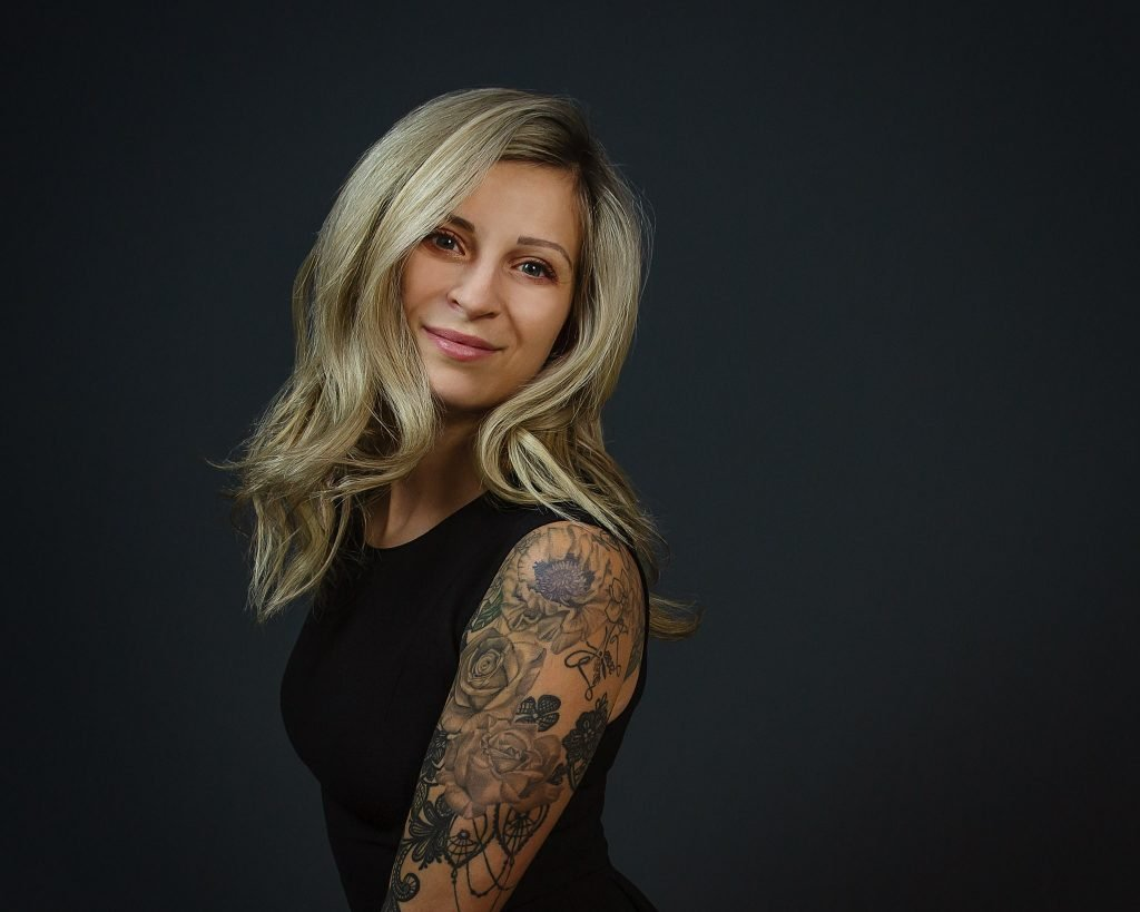 image of blonde woman with tattoos on arm in black dress