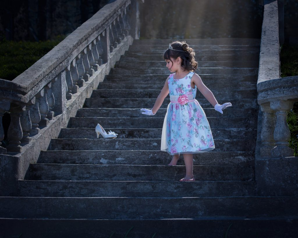 Fairy tale portrait of young girl in blue dress running down stairs with a glass slipper