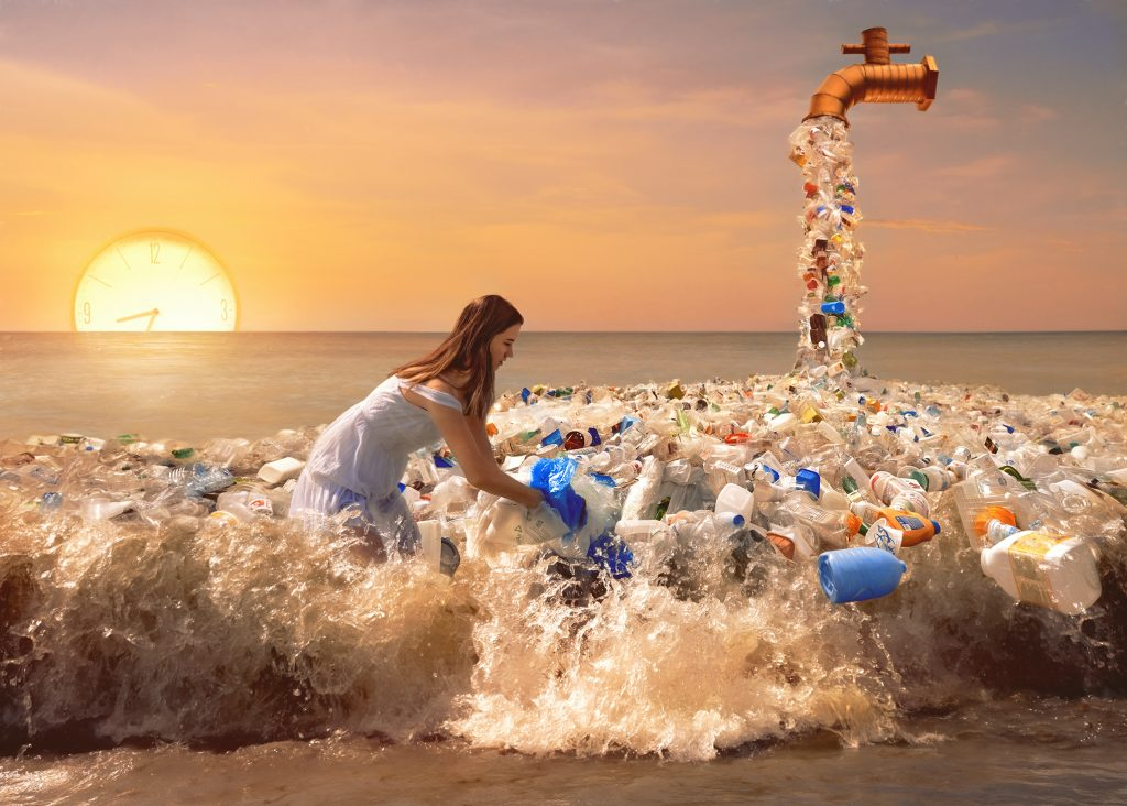 Photoshop composite image by Alana Lee of a girl trying to remove plastic waste from the water at sunset